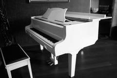 Vitt piano i det svarta rummet fotografering för bildbyråer