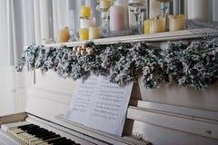Vitt piano med stearinljus Lyckligt begrepp för vinterferier Arkivfoton