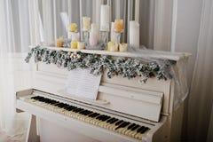 Vitt piano med stearinljus Lyckligt begrepp för vinterferier Fotografering för Bildbyråer