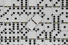 Vitt plast- domino med svart prickbakgrundsyttersida och en tom dominobricka i mitt av sammansättningen royaltyfri foto