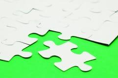 Vitt pussel på grön yttersida royaltyfri foto