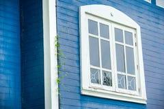 Vitt ramfönster med den blåa väggen på bakgrund royaltyfria foton