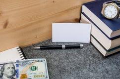 Vitt, rektangulärt pappers- ark för att skriva på bakgrunden av böcker, anteckningsböcker, pennor och dollar royaltyfri fotografi