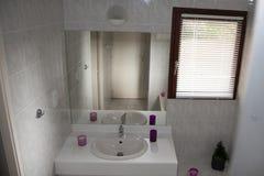 Vitt rent modernt minsta badrum i ett ljust hus Royaltyfri Foto