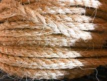 Vitt rep och att texturera - det rullade ihop vita repet på en högt texturerad träbakgrund Nautically themed studionärbild arkivfoto