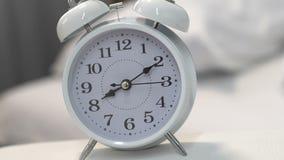 Vitt ringklockaanseende på near säng för tabell, stopptid, tidledning, closeup arkivfilmer