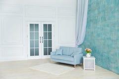Vitt rum är en blå soffa, en sockel med blommor i en vas royaltyfria bilder