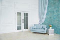 Vitt rum är en blå soffa, en sockel med blommor i en vas royaltyfria foton