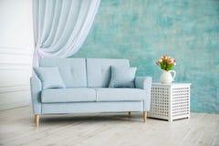 Vitt rum är en blå soffa, en sockel med blommor i en vas arkivfoton