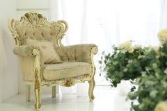Vitt rum med blommor och tappningstol Royaltyfria Bilder