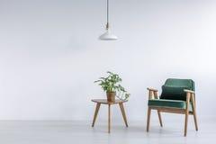 Vitt rum med den gröna fåtöljen arkivbild