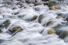 Vitt silkeslent vatten som nedströms flödar över, vaggar och stenblock royaltyfri foto