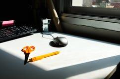 Vitt skrivbord i kontoret och solljuset Arkivfoton