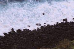 Vitt skum av havvatten nära kusten med mörka stenar Kust av ön av madeiran fotografering för bildbyråer