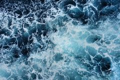 Vitt skum på yttersidan av det blåa havet Arkivbilder