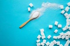 Vitt socker med skeden på blå bakgrund arkivfoton