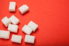 Vitt socker på en röd bakgrund, tomt utrymme för text arkivbild