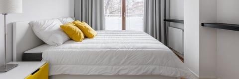 Vitt sovrum med dubbelsäng arkivbilder
