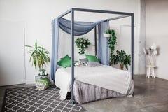Vitt sovrum med enkla dekorobjekt i strand utformad hem- lägenhet med grönska, husväxter royaltyfri fotografi