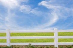 Vitt staket och grönt gräs på blå himmel arkivbilder