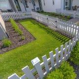 Vitt staket runt om en solbelyst landskap gård royaltyfri foto