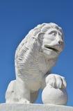 Vitt stenlejon med en sfär mot den blåa himlen Royaltyfri Foto