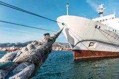 Vitt stort skepp som förtöjas i hamnport, selektiv fokus på att förtöja repet arkivbild