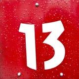 Vitt tecken för nummer tretton på en röd metallplatta Royaltyfria Foton