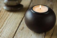 Vitt teljus i en svart wood stearinljushållare och zen balanserade stenar i bakgrund, copyspace för text, harmonibegrepp Arkivbild