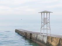Vitt träräddningsaktiontorn på vågbrytaren Seascape i mjuk bl Royaltyfri Fotografi