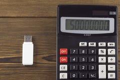 Vitt USB exponeringsdrev och en skrivplatta på en träbakgrundsusb arkivfoton