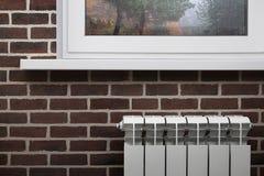 Vitt värma element på bakgrunden av den bruna tegelstenväggen under fönstret fotografering för bildbyråer