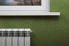 Vitt värma element på bakgrunden av den gröna väggen under fönstret arkivbild