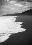 Vitt vatten på svart sand Fotografering för Bildbyråer