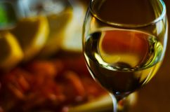 Vitt vin i ett exponeringsglas med aptitretare på en trätabell, en uppsättningnolla arkivbilder