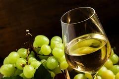 Vitt vin i ett exponeringsglas och gröna och röda druvor i en vide- baske royaltyfria bilder