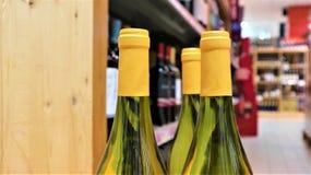 Vitt vin i flaskor i vin shoppar royaltyfri foto