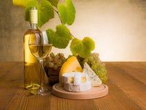 Vitt vin med druva- och ostmellanmålet royaltyfri bild