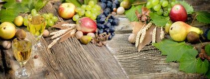 Vitt vin och höstlig frukt - skörd på tabellen royaltyfria foton