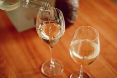 Vitt vin som häller in i exponeringsglaset ovanför sikt arkivbild