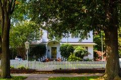 Vitt wood hus för två berättelse med pumpor för posteringstaket och en amerikanska flaggan som flankeras av två stora träd royaltyfri fotografi
