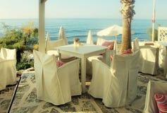 Vittabeller och stolar i det grekiska kafét vid havskusten, Kreta, G Arkivfoton