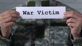 Vittima di guerra scritta su carta in mani del soldato maschio, concetto di PTSD, primo piano archivi video