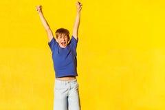 Vittoria! Le mani freckled emozionali del ragazzo aumentano e gridano Fotografia Stock