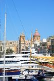 Vittoriosa marina, Malta. Yachts moored in the marina with views towards St Lawrence church and waterfront buildings, Vittoriosa, Malta, Europe Royalty Free Stock Images
