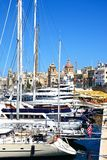 Vittoriosa marina, Malta. Yachts moored in the marina with views towards St Lawrence church and waterfront buildings, Vittoriosa, Malta, Europe Stock Image