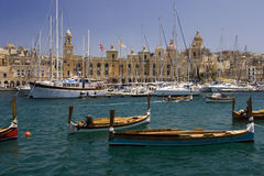 Vittoriosa - Valletta - Malta. Traditional Dghajsas or dicers moored in the harbor near the facade of the Maritime Museum in Vittoriosa one of the three cities Royalty Free Stock Image
