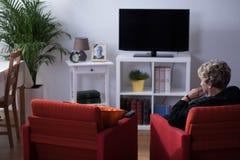 Viuda que se sienta en sala de estar Imagen de archivo libre de regalías