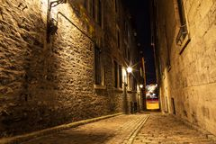 Viuzza e costruzioni storiche nel sito storico di vecchia porta da Montreal, visualizzazione di notte Fondo scenico del canadese immagini stock