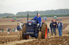 Viv Hughes, Ploughman. BASINGSTOKE, UK - OCTOBER 12, 2014: Viv Hughes competing on a vintage Fordson tractor in the second day of the British National Ploughing Stock Photography